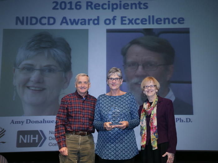 Amy Donahue, Ph.D. (center), with NIDCD Director James F. Battey, Jr., M.D., Ph.D. (left), and NIDCD Deputy Director Judith Cooper, Ph.D. (right).