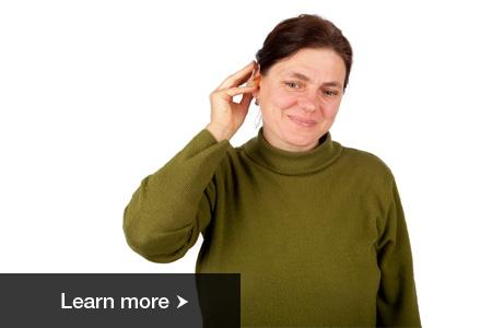 A woman smiling with her hand up to her ear, touching her hearing aid.